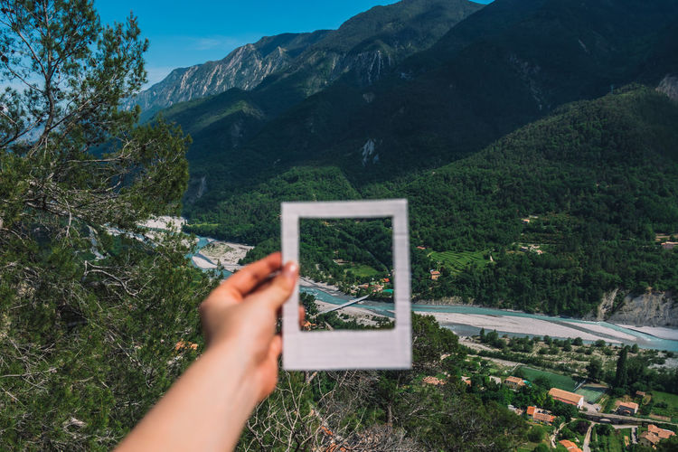 Cropped hand of woman holding picture frame against landscape