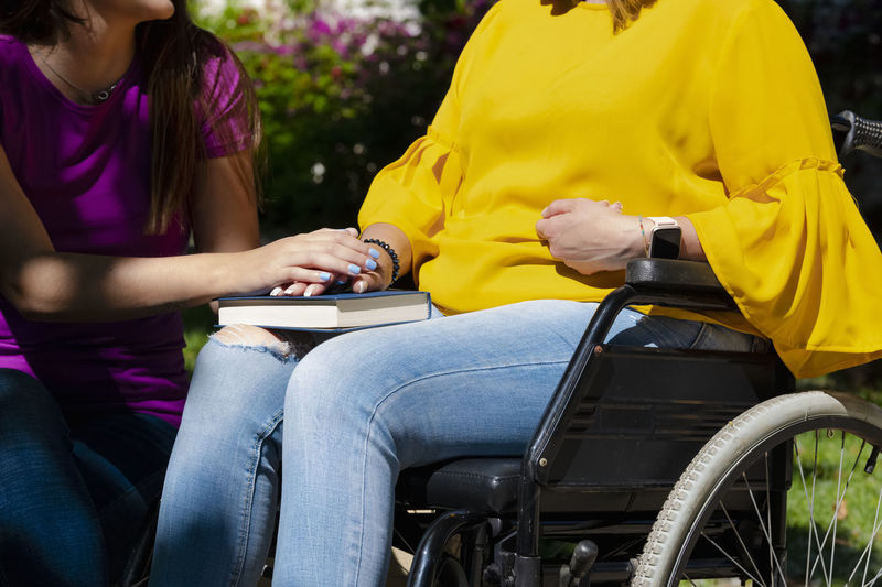Daughter consoling mother sitting on wheelchair with book