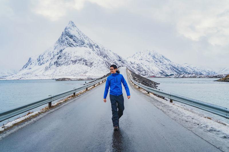 Full length of man walking on bridge over river during winter