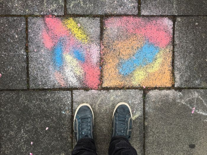 Low section of man standing by colorful paved footpath