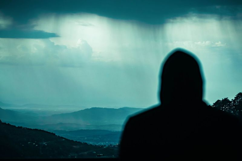 Rear view of silhouette man looking at mountains against sky