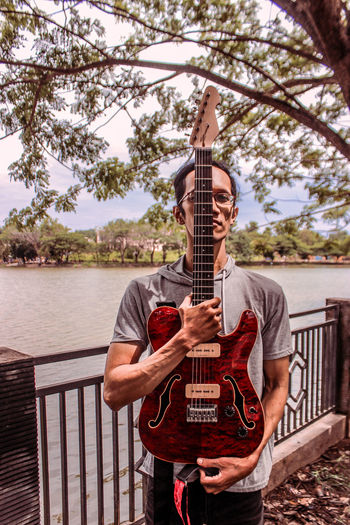 Man playing guitar on railing