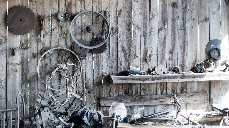 Old workshop with tools, broken bicycles wheels and saw blades hanging on wooden walls Abandoned Close-up Day Equipment Factory No People Outdoors Rusty Tools Vintage