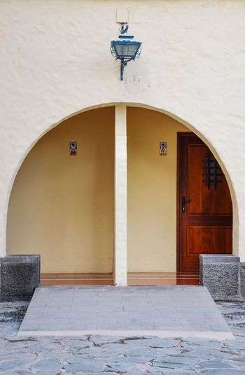 Quite the Entrance Shapes And Forms Entrance Building Quite The Entrance Wooden Door Beige Sand Color Archway Built Structure Door Architecture No People Day Building Exterior Outdoors
