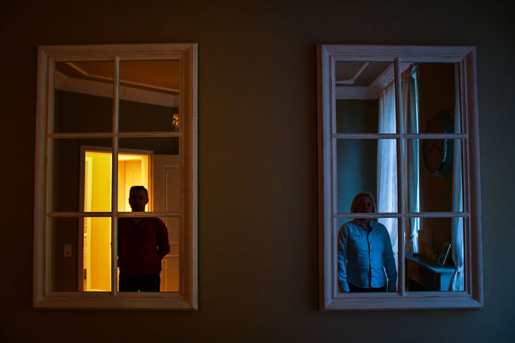 Woman and man standing by window at home building
