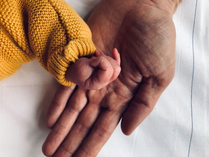 Bright Top Perspective Top View Baby Comparison Males  Man Yellow Tiny Small New Born EyeEm Selects Human Hand Hand Human Body Part Adult Indoors  Holding Body Part Close-up Real People Human Finger Textile Childhood Holding Hands Finger