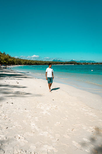 Man walking on beach against blue sky