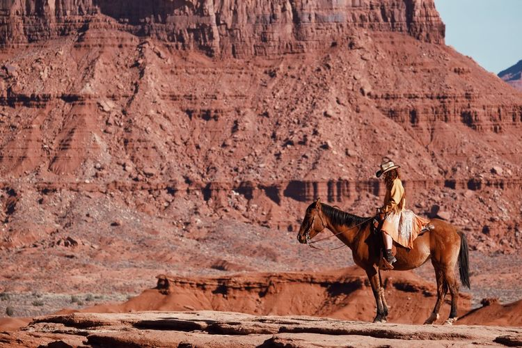 Side view of woman riding horse against rock formation