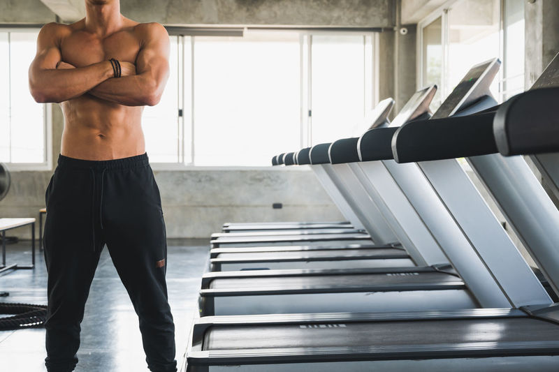 Midsection of shirtless man standing by treadmills in gym