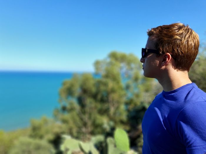 Young man wearing sunglasses against sea and blue sky
