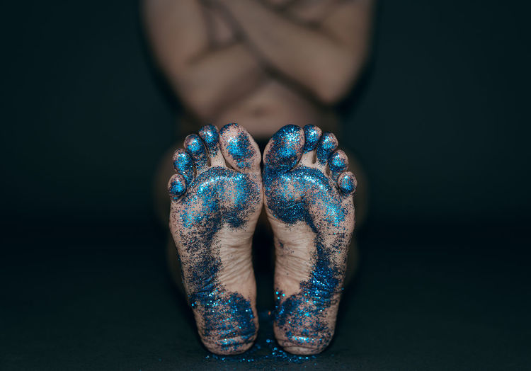Low section of woman barefoot covered in glitter over black background