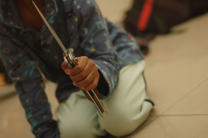 Close-Up Of Boy Holding Knife While Kneeling On Floor