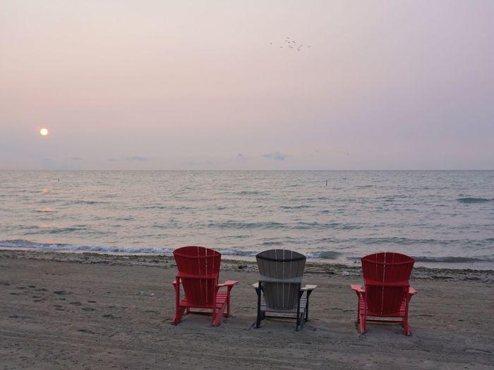 Chair on beach against sky during sunset
