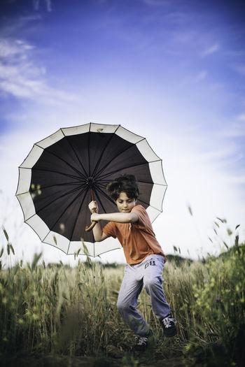 Boy Holding Umbrella While Running On Grassy Field