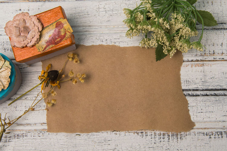 Decorated gift boxes next to blank brown paper on wooden background Copy Space Rustic Background Blank Paper Brown Dried Flowers Flowers Gift Message Paper Present Shabby Chic Text Space Vintage Wooden