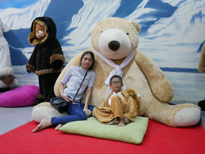 Portrait of mother and son sitting against large teddy bear