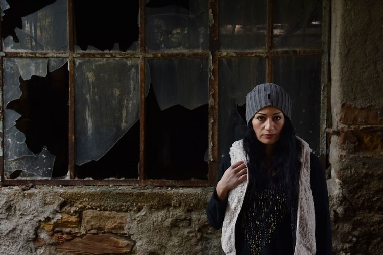 Woman standing against abandoned building