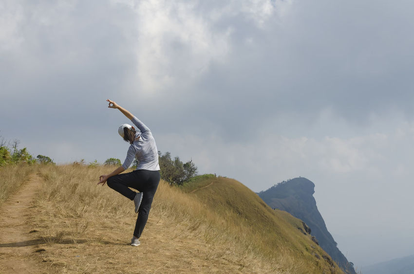 Young girl doing yoga on the mountain. Adventure Backpack Beauty In Nature Cloud Cloud - Sky Cloudy Day Freedom Full Length Hill Landscape Lifestyles Mountain Nature Outdoors Sky Yoga Yoga In Nature Yoga Pose
