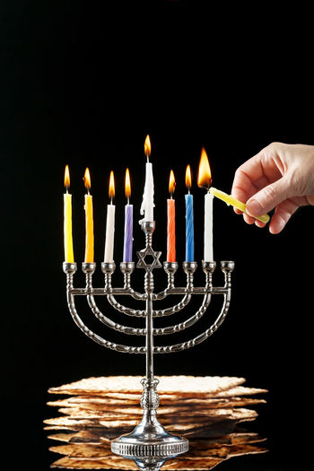 Menorah with lighted candles for Hanukkah on a black in the background. Birthday Cake Birthday Candles Black Background Body Part Burning Cake Candle Chanuka Chanukah Close-up Culture Finger Fire Fire - Natural Phenomenon Flame Hand Hanukkah Heat - Temperature Human Body Part Human Hand Indoors  Matchstick Matzo Matzoth Menorah One Person Studio Shot