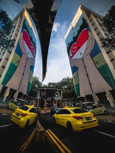 Singapore HDB Flat Singapore Taxi Reflection Mirror Transportation Car Mode Of Transportation Motor Vehicle City Architecture Land Vehicle Building Exterior Road Built Structure Street Sky No People Travel Sign Road Marking Day Flag The Creative - 2018 EyeEm Awards