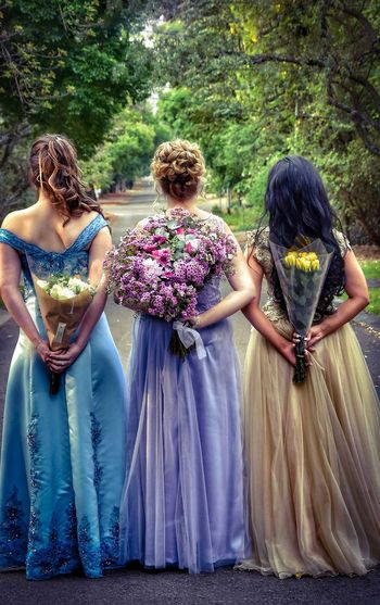 Rear view of women standing with flowers