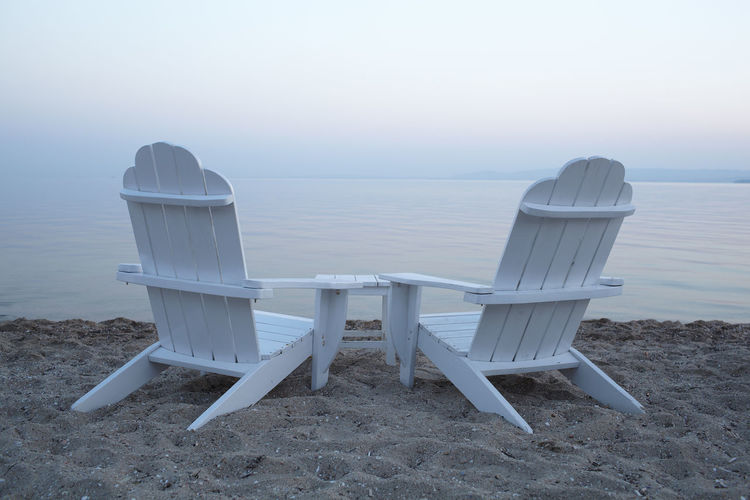White adirondack chairs on sand at beach against sky during sunset