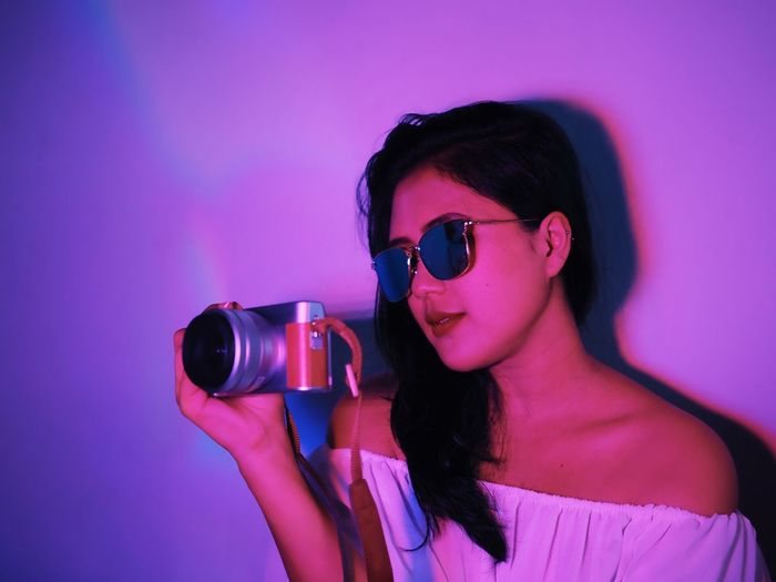 One Person Photography Themes Real People Camera - Photographic Equipment Young Adult Holding Technology Pink Color Leisure Activity Indoors  Young Women Front View Lifestyles Photographing Headshot Women Fashion Glasses Portrait Purple Beautiful Woman Digital Camera Hairstyle Photographer