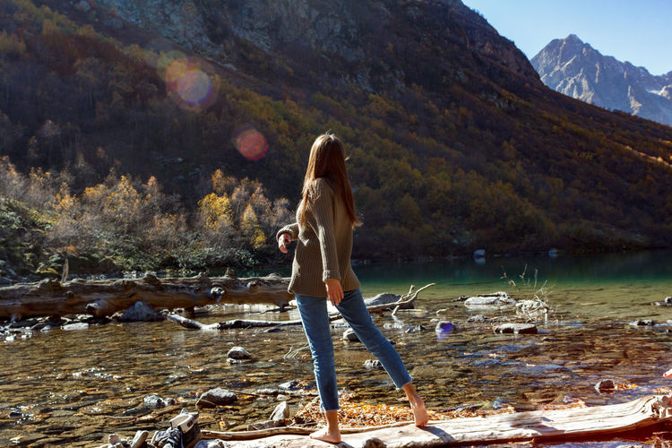 Woman standing by lake against mountain