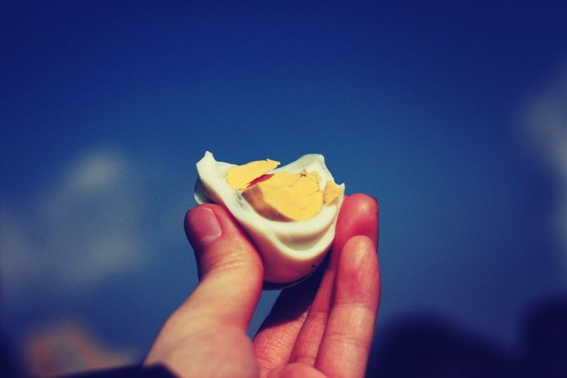 Cropped Image Of Hand Holding Boiled Egg