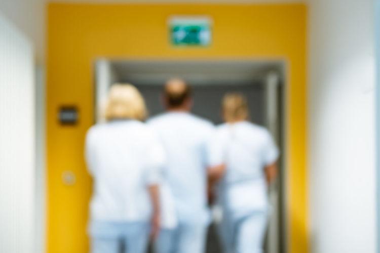 Rear view of people standing by door
