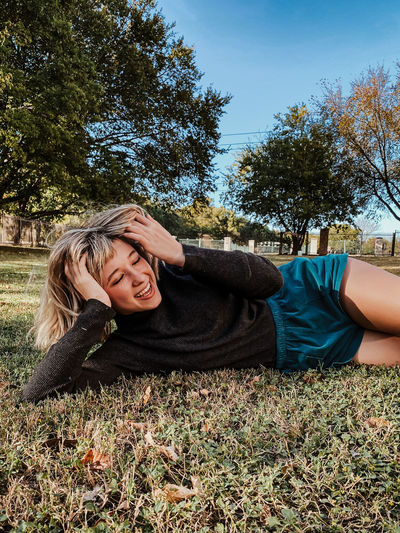 Portrait of smiling woman lying down on field