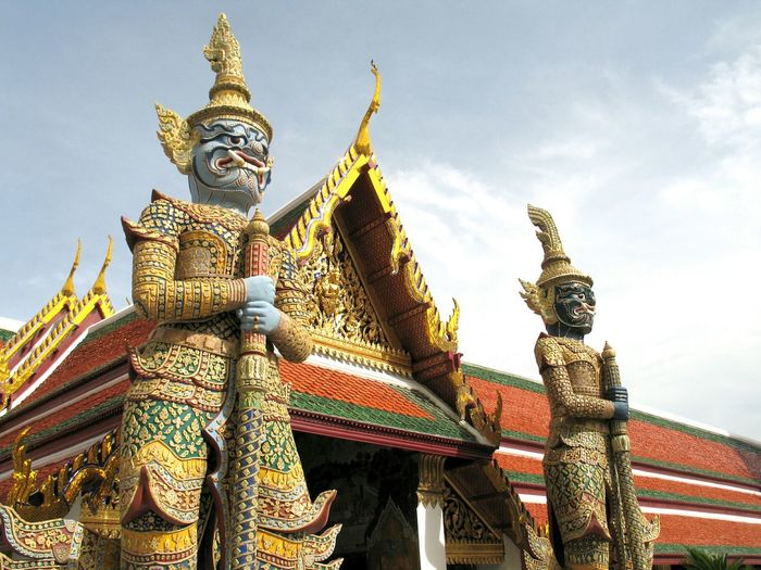 Low Angle View Of Demon Statues At Wat Phra Kaew Against Sky