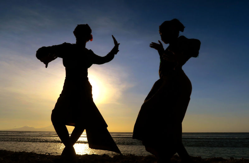 Silhouette women dancing at beach against sky