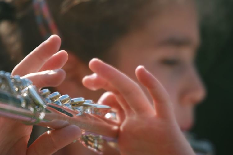 Close-up of boy playing flute