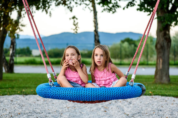 Sisters sitting on swing at park