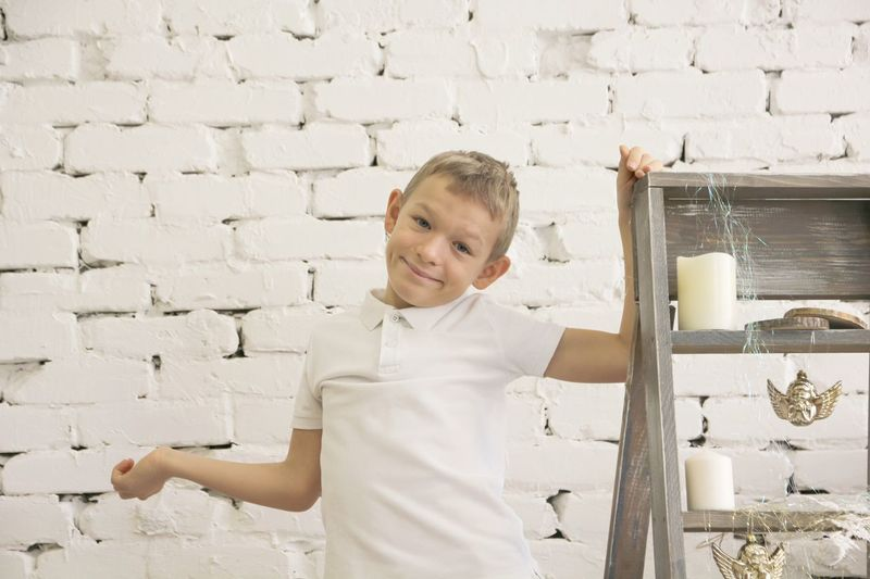 Boy standing against wall