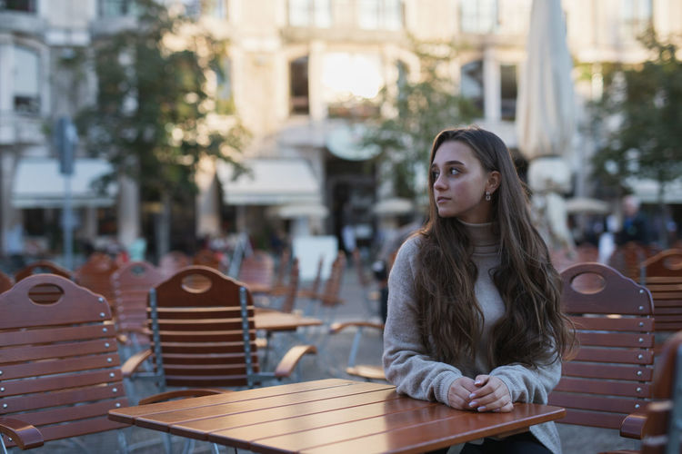 Young woman sitting on table in city