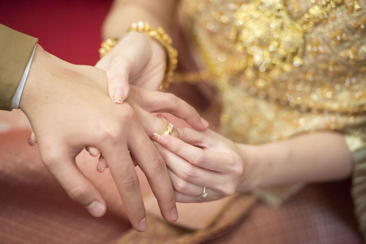 Cropped image of bride putting ring on bridegroom finger during wedding ceremony