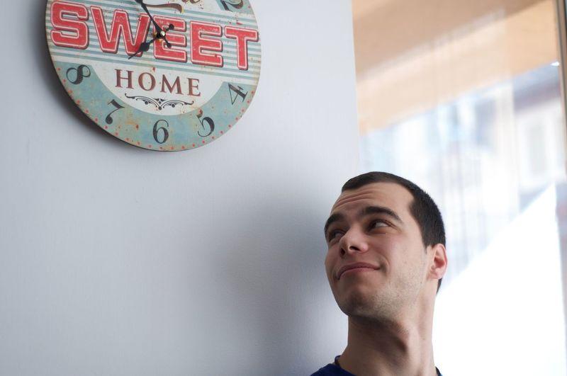 Man looking at clock against wall