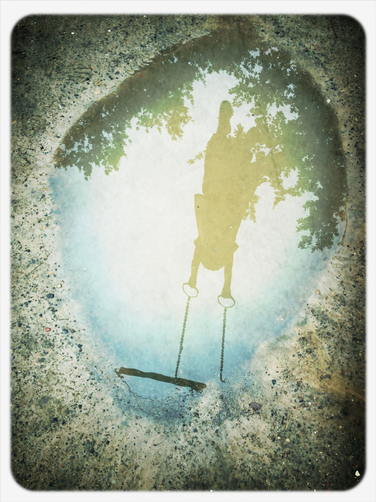 Reflection of girl swinging in puddle