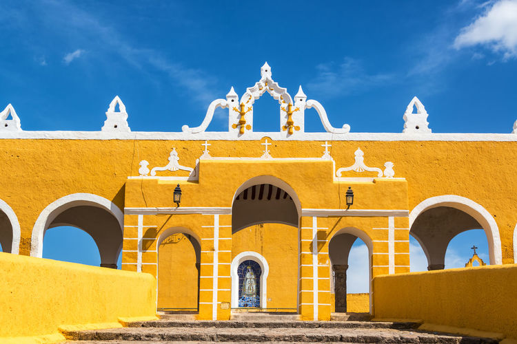 Low angle view of yellow monastery against sky