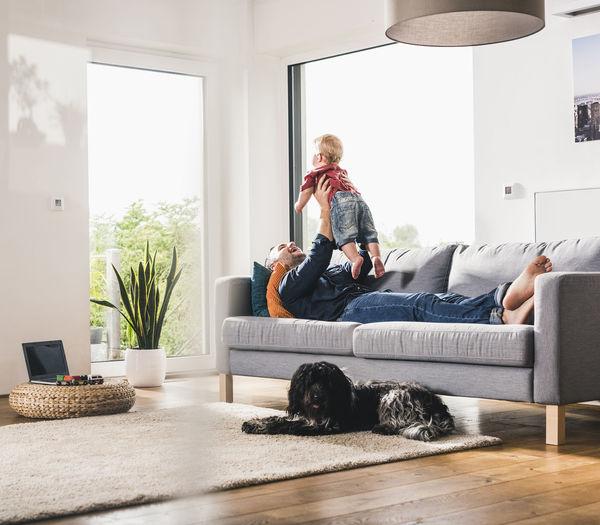 Man and dog on sofa at home