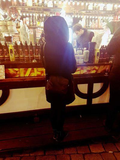 Full length of man standing at illuminated restaurant at night