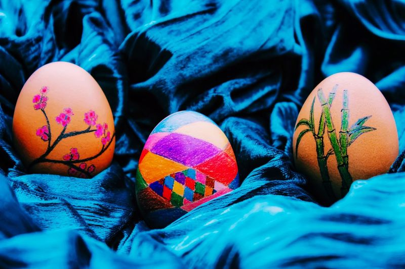 Close-Up Of Painted Easter Eggs On Blue Fabric