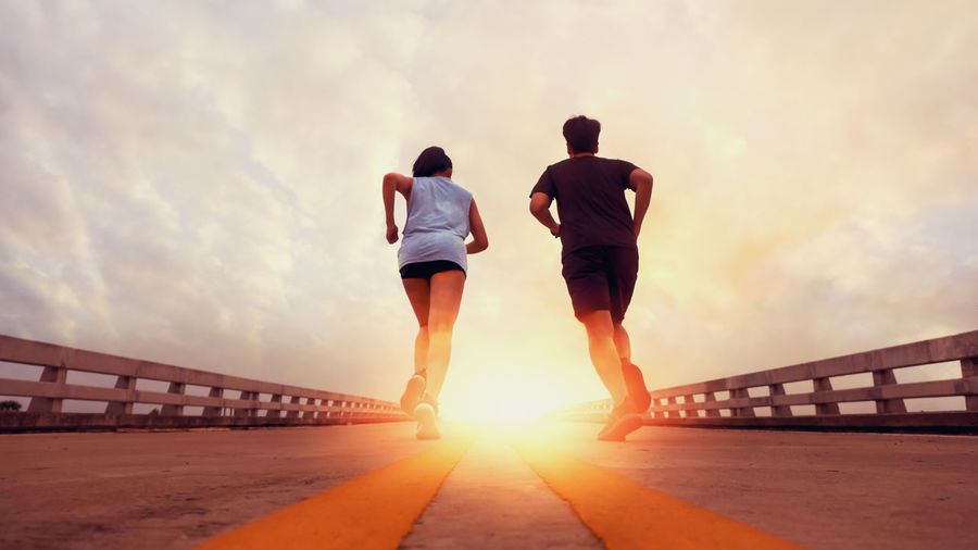 Two runners ran outside. And running on jogging roads. The concept of creating good health Sky Rear View Sunset Lifestyles Men Architecture Nature Bridge Full Length Real People Leisure Activity Two People Sunlight Built Structure Cloud - Sky Women Togetherness People Railing Bridge - Man Made Structure Sun Outdoors Lens Flare Couple - Relationship