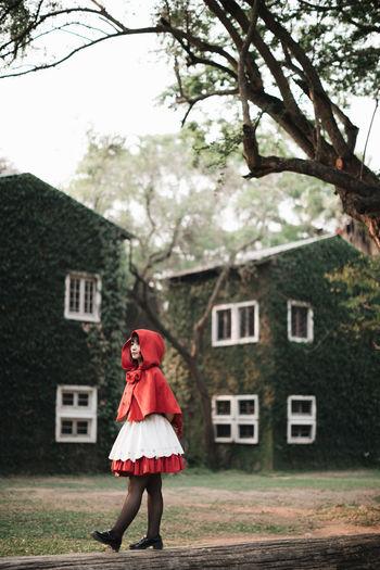 Full length of woman walking on log against house