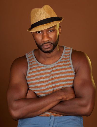 Portrait Of Man Wearing Hat Against Colored Background