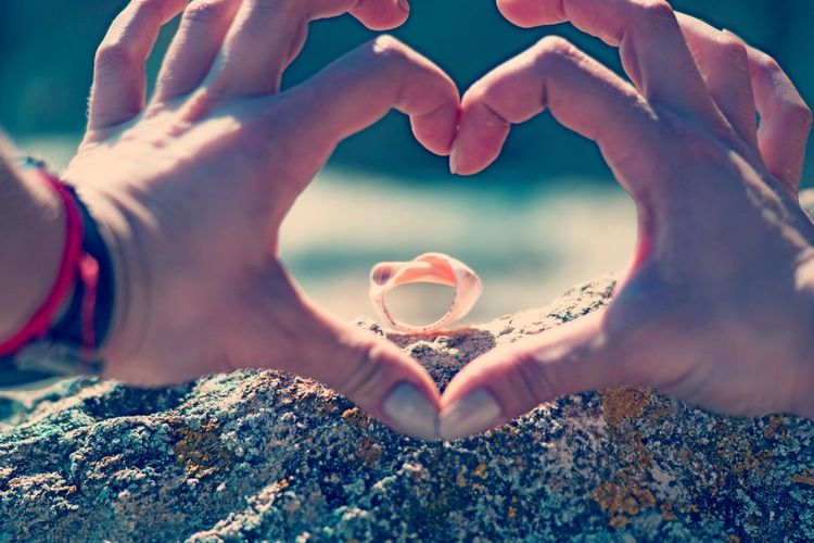 Cropped hands of woman making heart shape by shell on rock