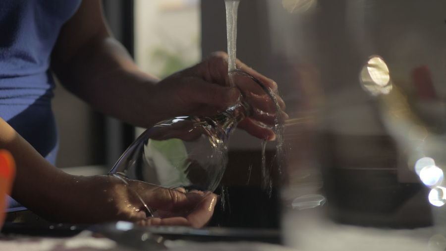 Midsection of woman cleaning wineglass