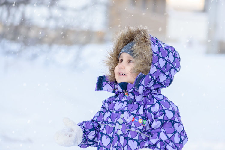 Girl standing on snow covered field during snowfall